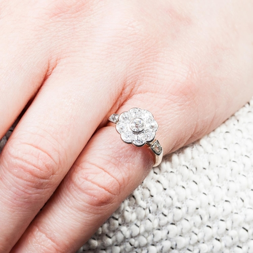51 - AN ANTIQUE DAISY CLUSTER RING with old cut diamonds of approx. 1.20 ct in total, H, VS, mounted in y...