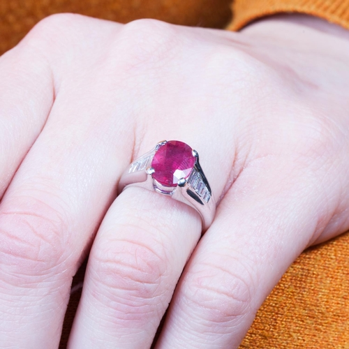 57 - A RUBY SINGLE STONE RING, to tapered baguette diamond shoulders, mounted in platinum. Estimated; wei...