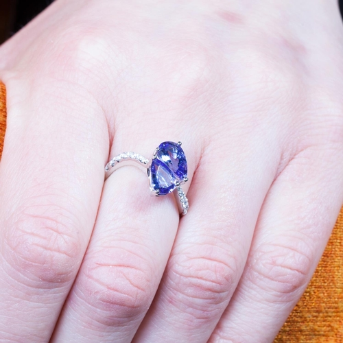 58 - A TWO STONE TANZANITE RING, of cross over design, the pear shaped tanzanite to diamond shoulders, mo...