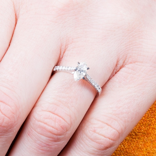 59 - A DIAMOND SOLITAIRE RING, the marquise cut diamond to diamond shoulders, mounted in 18ct white gold....