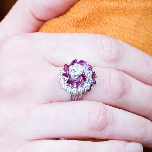 6 - A DIAMOND AND RUBY CLUSTER RING, the central pear shaped diamond estimated to weigh 0.50ct, mounted ...
