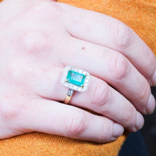 7 - AN EMERALD AND DIAMOND CLUSTER RING, the central emerald surrounded by diamonds. Estimated weight of...