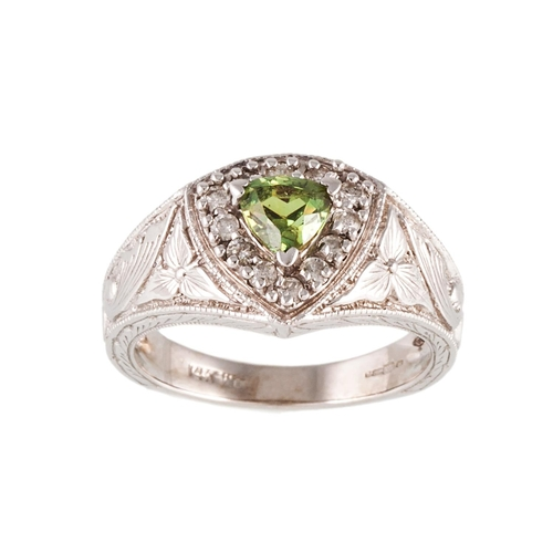 26 - A PERIDOT AND DIAMOND CLUSTER RING, to a 14ct white gold carved mount...