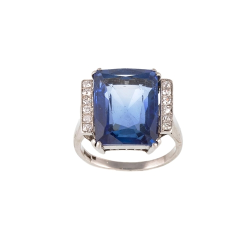 8 - AN ART DECO SAPPHIRE AND DIAMOND DRESS RING, the radiant cut sapphire mounted in white metal. Estima...