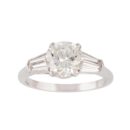 156 - A DIAMOND SOLITAIRE RING, the round brilliant cut diamond to tapered baguette diamond shoulders. Est...