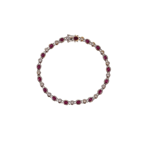 241 - A RUBY AND DIAMOND LINE BRACELET, the circular cut stones collet set in 18ct white gold...