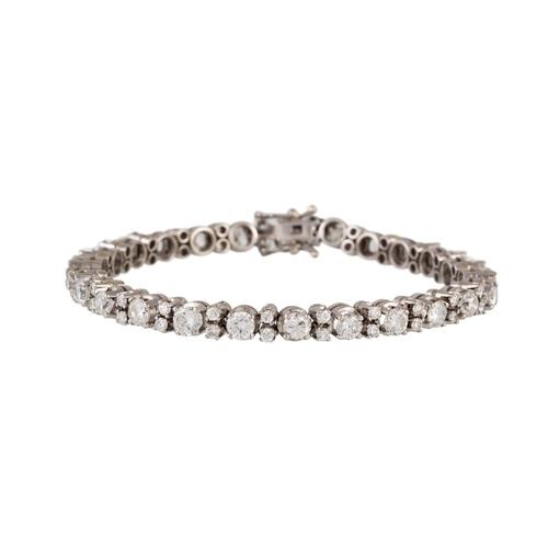 243 - A DIAMOND LINE BRACELET, each brilliant cut diamond set between two smaller diamonds, mounted in whi...