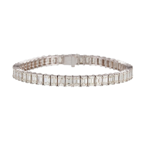 254 - A DIAMOND LINE BRACELET, the emerald cut diamonds mounted in 18ct white gold. Estimated; weight of d...