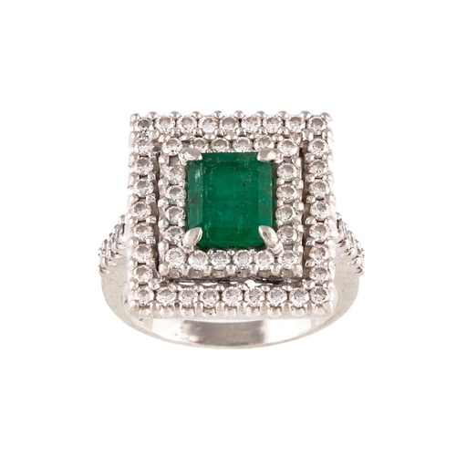 3 - AN EMERALD AND DIAMOND CLUSTER RING, the trap cut emerald to a diamond surround, mounted in platinum...