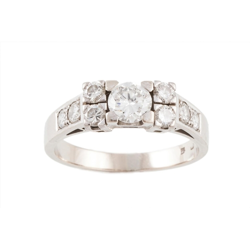 424 - A DIAMOND RING, with centre diamond of approx. 0.85ct, F/G VS1. Diamonds to either side and diamond ...