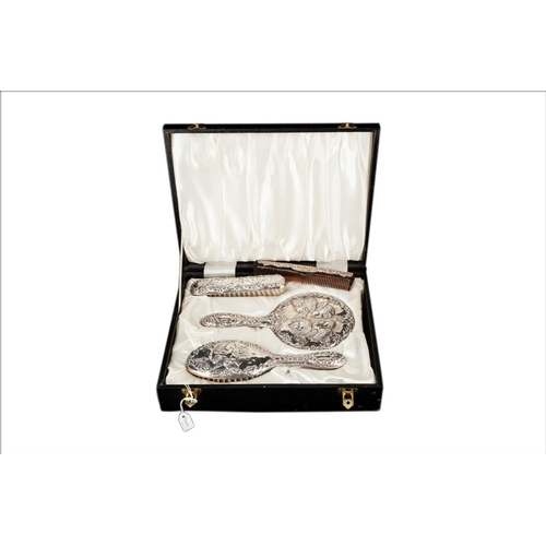 537 - AN EDWARDIAN STYLE SILVER EMBOSSED FOUR PIECE DRESSING TABLE SET, comprising of a hairbrush, clothes...