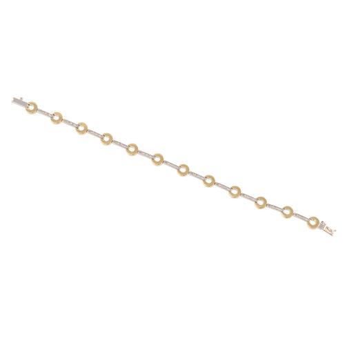 35 - A DIAMOND BRACELET, the circular links set between diamond bars, two colour 18ct gold. Estimated; we...