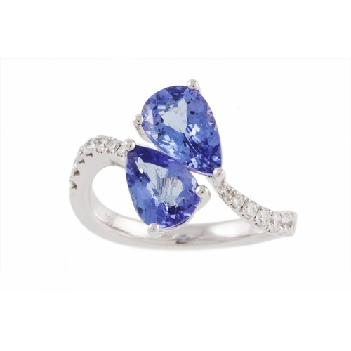 39 - A TWO STONE TANZANITE RING, of cross over design, the pear shaped tanzanite to diamond shoulders, mo...