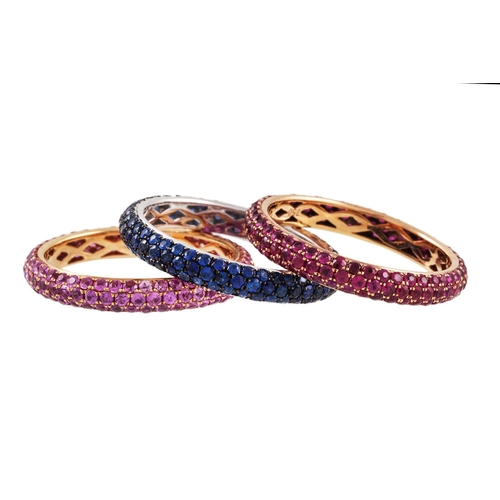 41 - THREE FULL BANDED ETERNITY RINGS, , by Gioielli, set with ruby and pink and blue sapphires, mounted ...