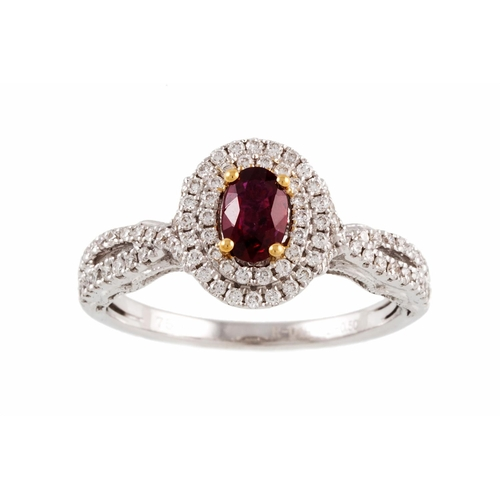 43 - A RUBY AND DIAMOND CLUSTER RING, the oval ruby to diamond surround and shoulders, mounted in white g...