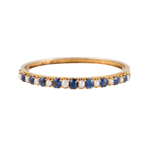 54 - AN ANTIQUE SAPPHIRE AND PEARL HINGED BANGLE, set with alternating oval sapphires and pearls, mounted...