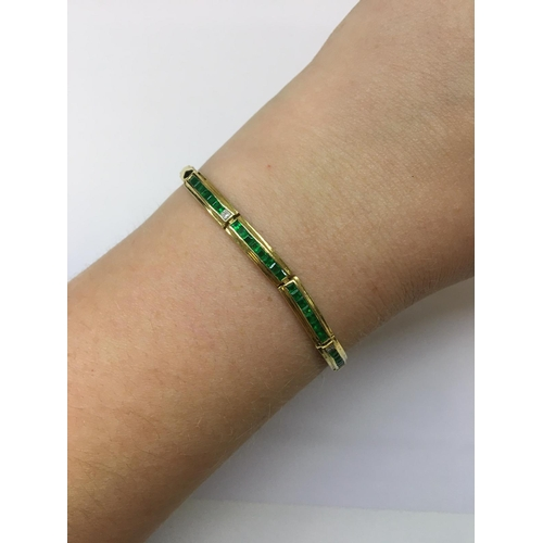 53 - A DIAMOND AND EMERALD BRACELET, channel set with emeralds and diamonds, mounted in 18ct yellow gold...