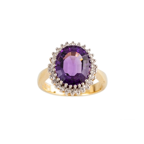 11 - A DIAMOND AND AMETHYST CLUSTER RING, the oval amethyst to a brilliant cut diamond surround, mounted ...