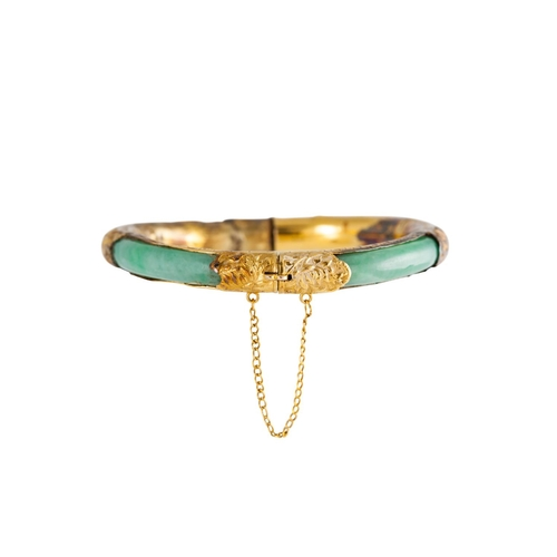 20 - A JADE BANGLE, with Chinese motifs, 14ct yellow gold mounted...