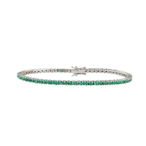29 - AN EMERALD LINE BRACELET, the circular stones mounted in white gold. Estimated; weight of diamonds; ...