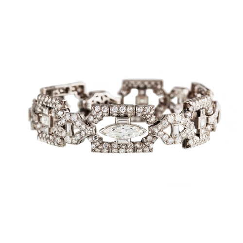41 - AN EARLY 20TH CENTURY DIAMOND PLAQUE BRACELET, of openwork geometric design, set throughout with mar...