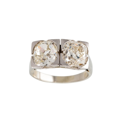55 - AN ART DECO TWO STONE DIAMOND RING, the old cut diamonds mounted in white metal. Estimated; weight o...