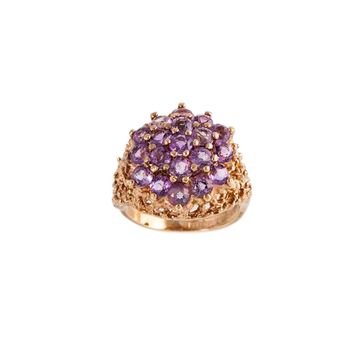 9 - AN AMETHYST CLUSTER RING, the circular amethysts mounted in a 9ct yellow gold textured mount, size I...