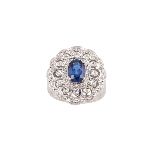 39 - A DIAMOND AND SAPPHIRE CLUSTER RING, the oval sapphire to an openwork diamond set plaque surround, m...