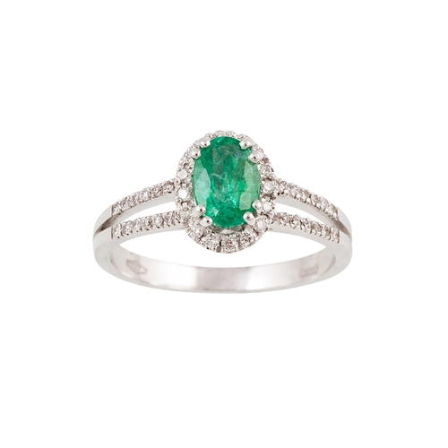 42 - A DIAMOND AND EMERALD CLUSTER RING, the oval emerald to a brilliant cut diamond surround, to split d...