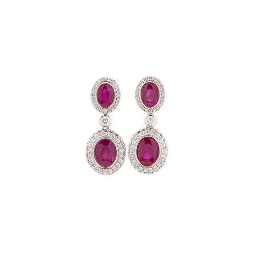 45 - A PAIR OF RUBY AND DIAMOND CLUSTER EARRINGS, each comprising an oval ruby and diamond cluster suspen...