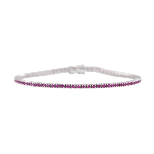 129 - A RUBY LINE BRACELET, set with circular stones, mounted in 18ct white gold. Estimated; weight of dia...