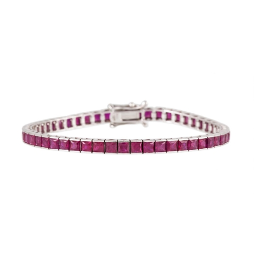 297 - A RUBY LINE BRACELET, set with square step cut rubies, channel set in 18ct white gold. Estimated; we...
