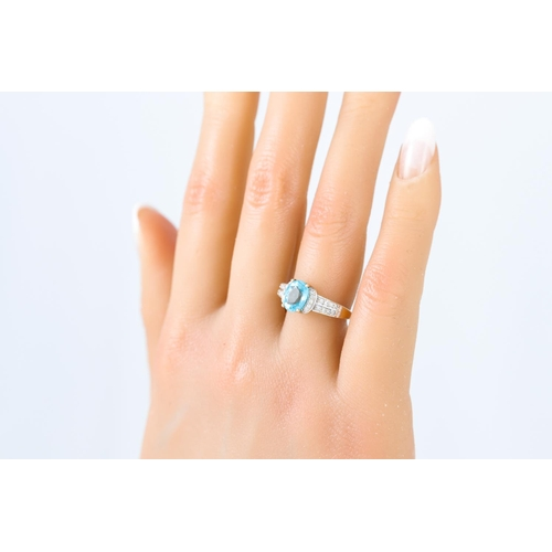 9 - A BLUE TOPAZ AND DIAMOND RING, the oval topaz to diamond shoulders, mounted in 9ct yellow gold, size...