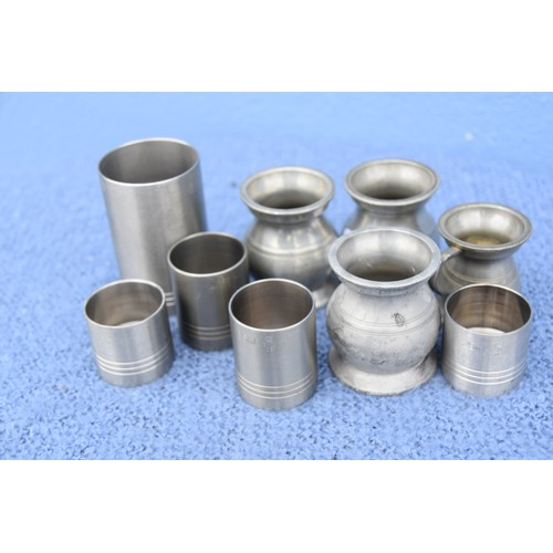 411 - A QUANTITY OF PEWTER DRINKS MEASURES