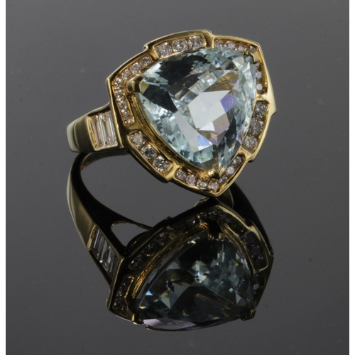 44 - 18ct yellow gold ring set with central trillion cut Paraiba tourmaline weighing 10.74ct surrounded b...