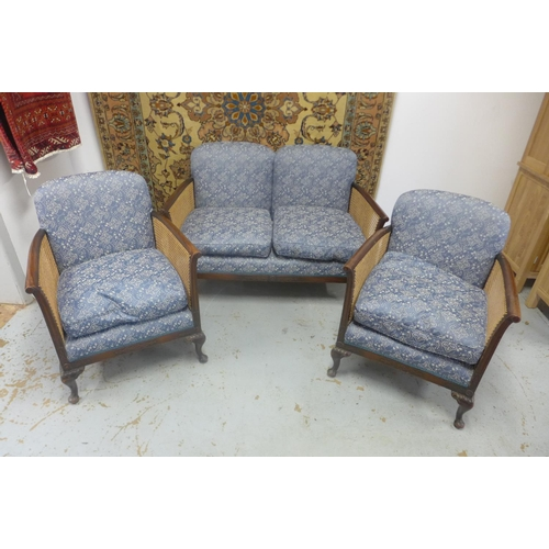 11 - An upholstered bergere three piece suite - settee is 121cm W x 80cm H x 70cm D...