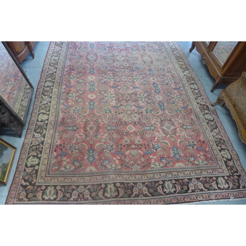 40 - A hand knotted woollen rug from Iran with a red field - 376cm x 288cm - general patches of wear and ...