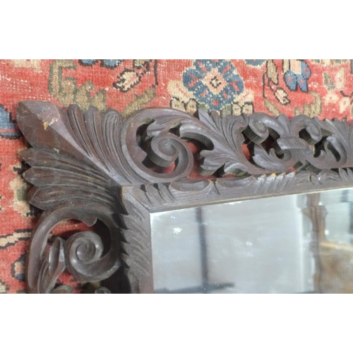46 - A carved oak wall mirror with acanthus carving - 114cm x 92cm...