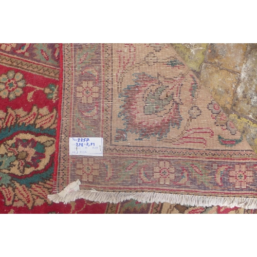 53 - A hand knotted woollen rug from Iran - with a red field - 398cm x 291cm - no obvious holes...