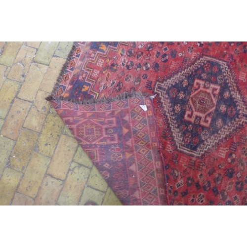 57 - A hand knotted woollen rug with a red field, colours bright, some general wear mainly to edges - 2.4...