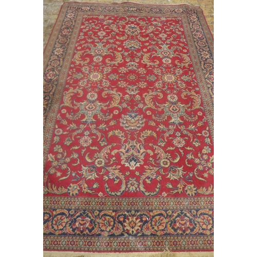 8 - A machine made woollen rug with a red field - 295cm x 200m - some general usage wear, colours bright...