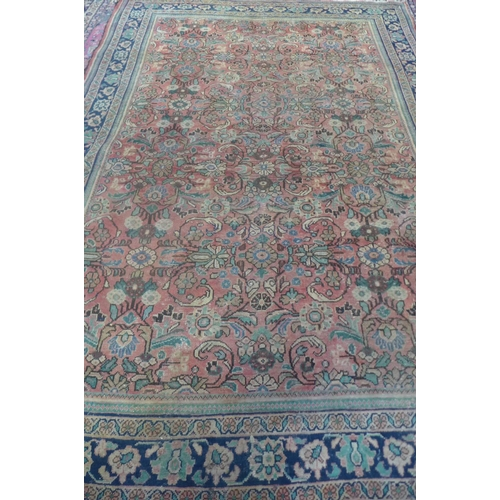 62 - A hand knotted woollen rug with light red ground, approx 362cm x 255cm, in used condition, with some...