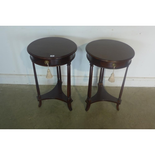 35 - A pair of mahogany circular side tables each with a drawer, 71cm tall, 45cm diameter...