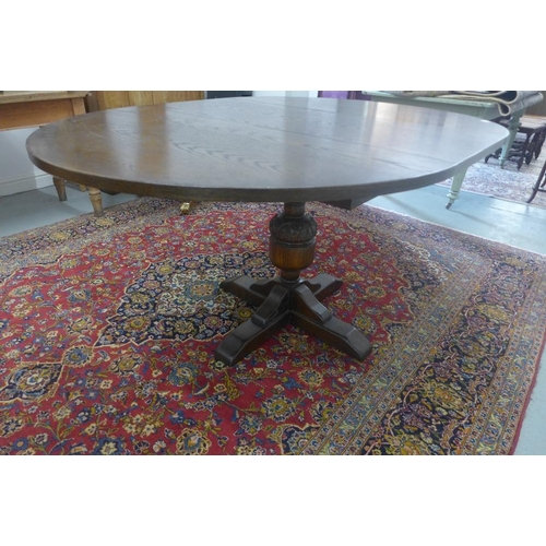 36 - A Jaycee oak pull out extending dining table, on a single carved bulbous support, 77cm tall x 156cm ...