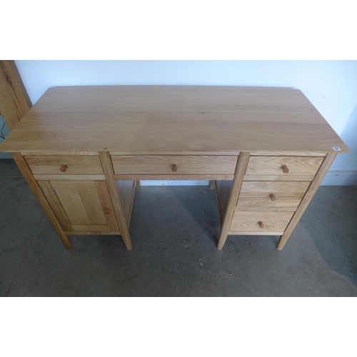 54 - An oak Oslo desk with five drawers and a cupboard, as new condition, retails at £399 - 82cm tall x 1...