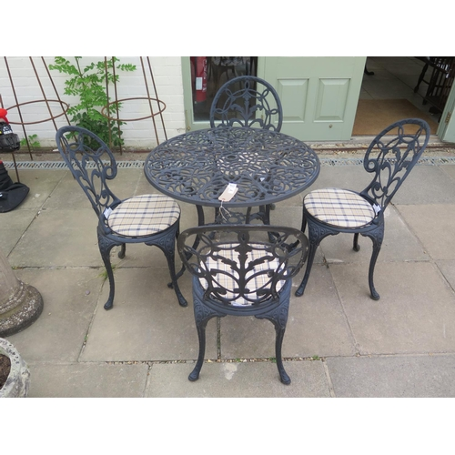 7 - An aluminium garden table and chairs with seat pads, table 81cm diameter...
