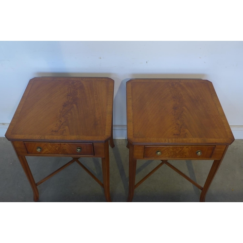 19 - A pair of fruit wood veneered lamp tables, with a single drawer, on splayed legs, united by cross st...