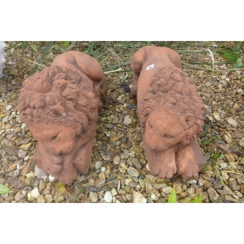 10 - A pair of cast stone terracotta recumbent lions on rectangular bases, after canova, 45cm L x 19cm H...