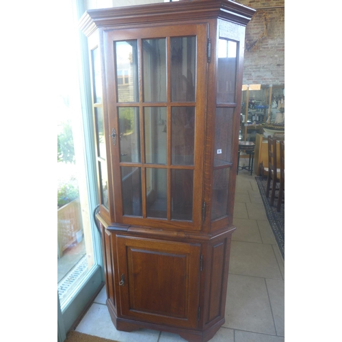 51 - A clover oak corner cupboard with a glazed door above a slide and a paneled cupboard door, 200cm tal...