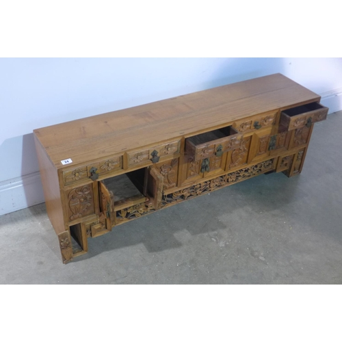 24 - A carved elm Chinese cabinet with five small drawers above six cupboard doors and two hidden compart...
